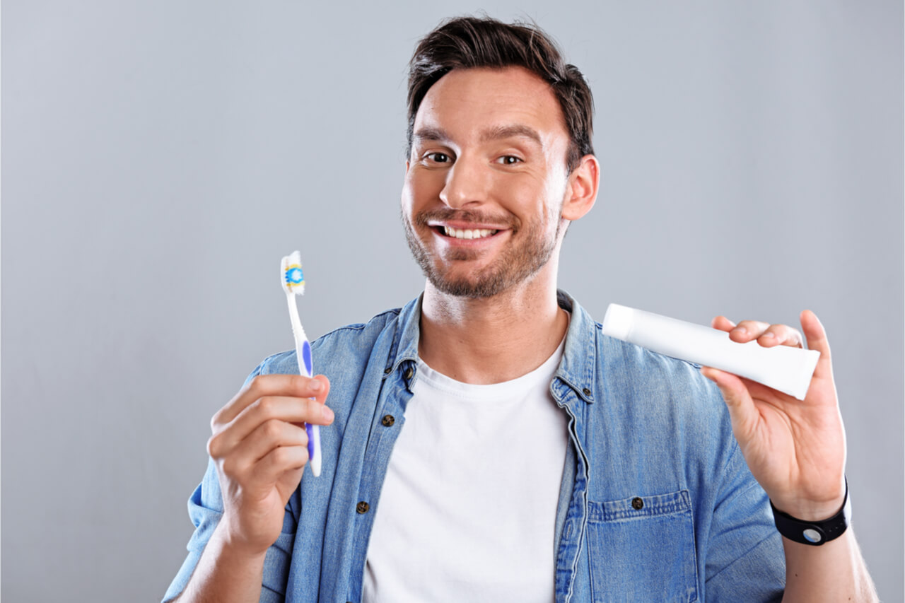 man holding toothpaste and toothbrush