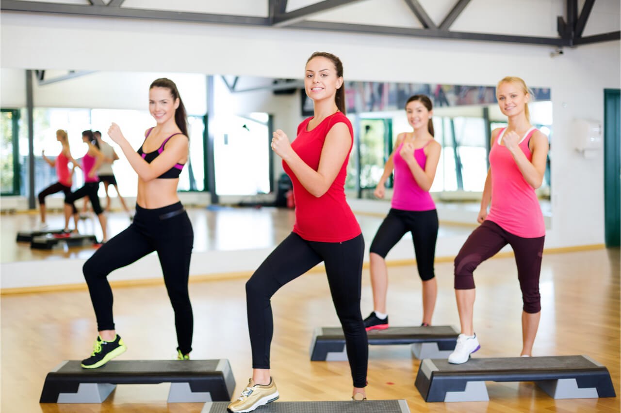 The group of women enjoy the step aerobics routine.