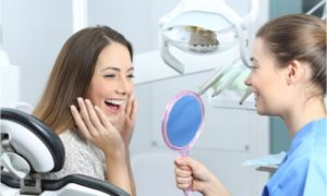 The dentist holds the mirror while the patient looking at her teeth.
